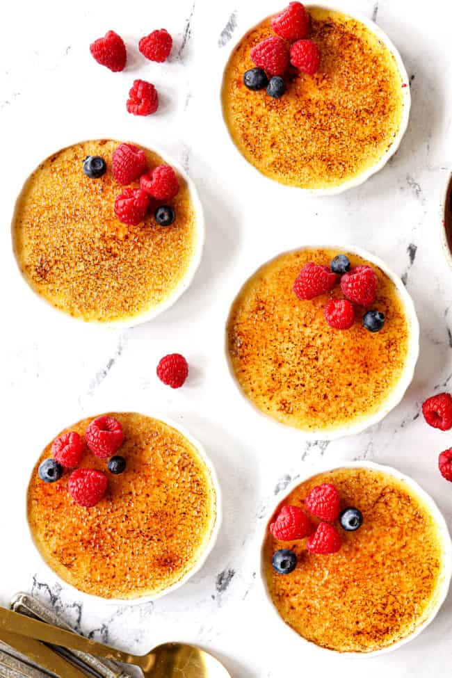 showing how to garnish creme brûlée recipe with top view of creme brulee with raspberries and blueberries