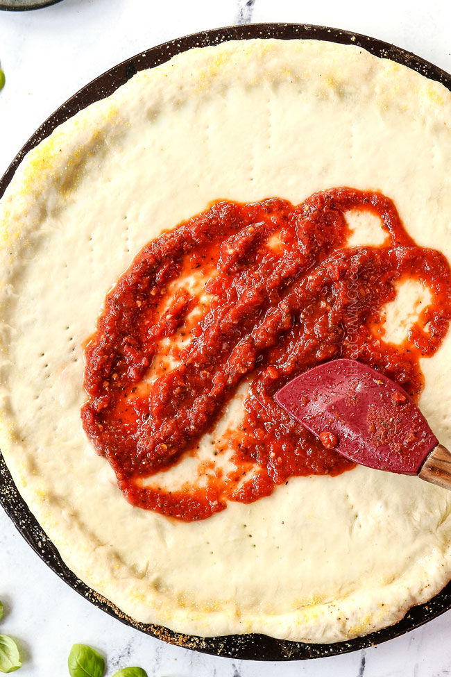 showing how to make pizza dough by adding pizza sauce before baking
