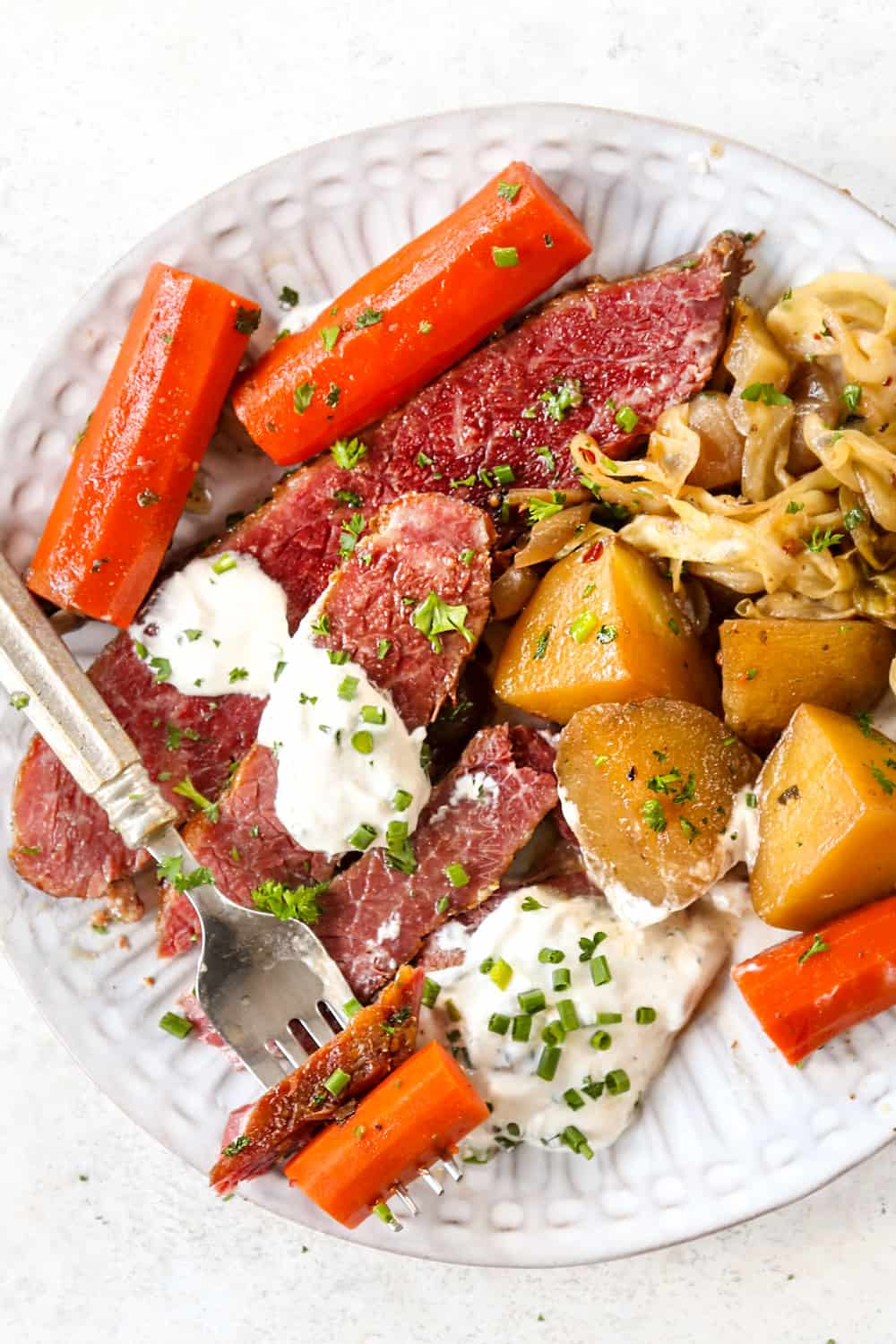 top view of corned beef brisket sliced on a white plate with cabbage, potatoes and carrots