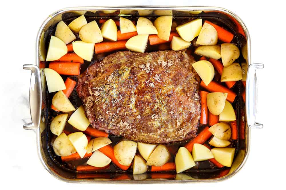 showing how to cook corned beef by adding brisket to a roasting and surrounding with carrots and potatoes