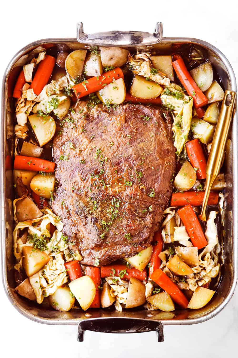 showing how to cook corned beef by roasting in a pan in the oven with cabbage, carrots and onions