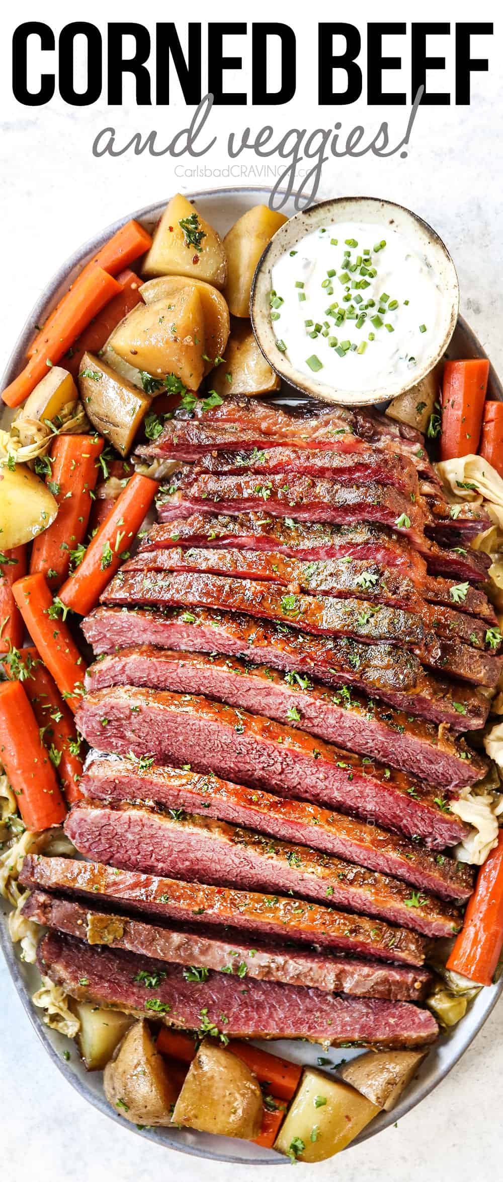 top view of corned beef and cabbage on a platter with potatoes, carrots and horseradish sauce