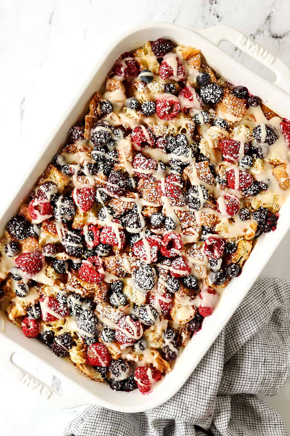 top view of croissant breakfast casserole with berries in a white casserole dish