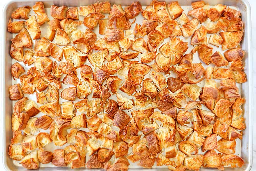 showing how to make breakfast casserole by toasting croissants on a baking dish