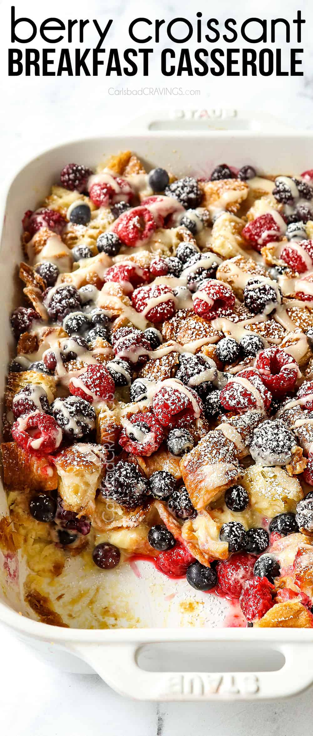 top view of sweet breakfast casserole with croissants, berries and lemon drizzle in a white casserole dish