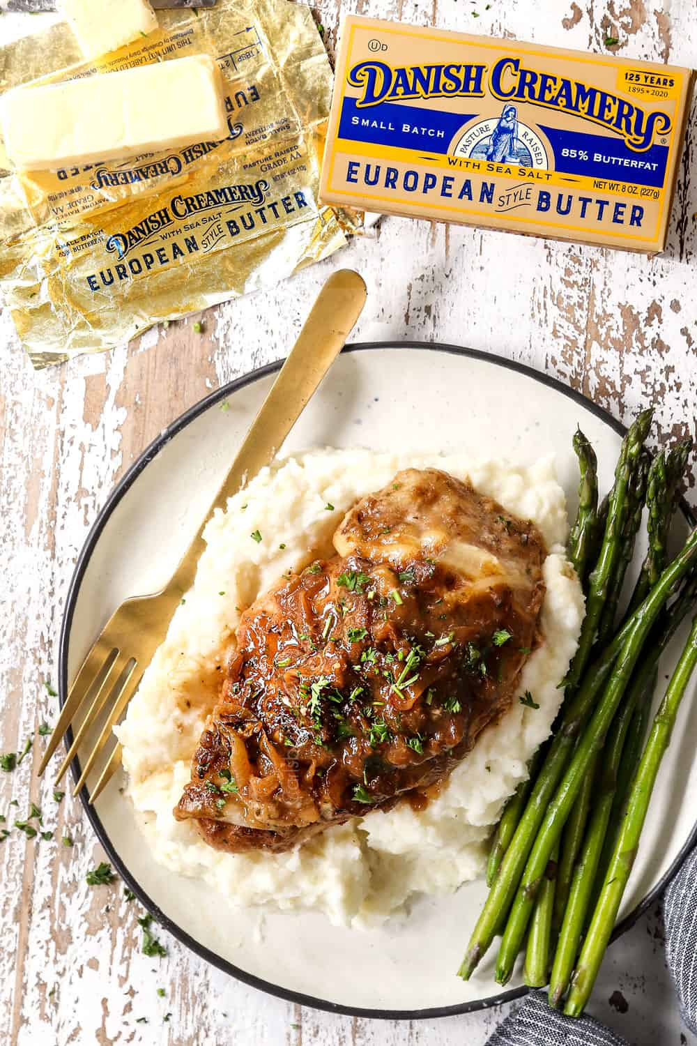 top view of a piece of French onion chicken on a plate with mashed potatoes with asparagus