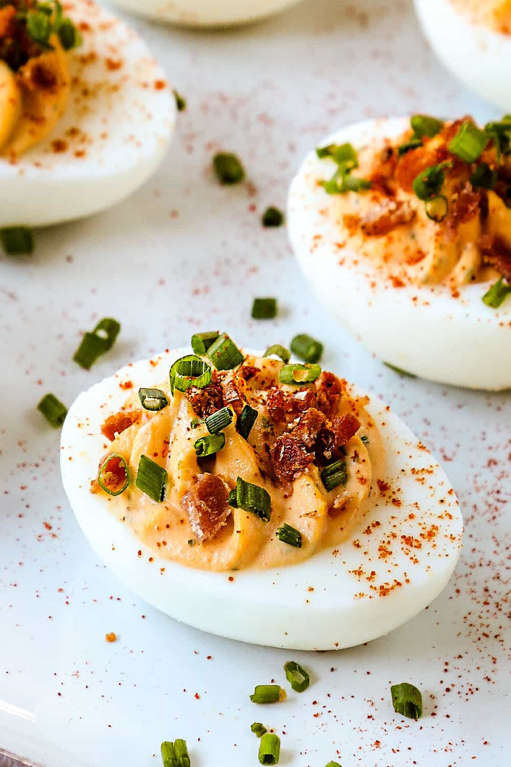 up close of best deviled eggs garnished with bacon and chives