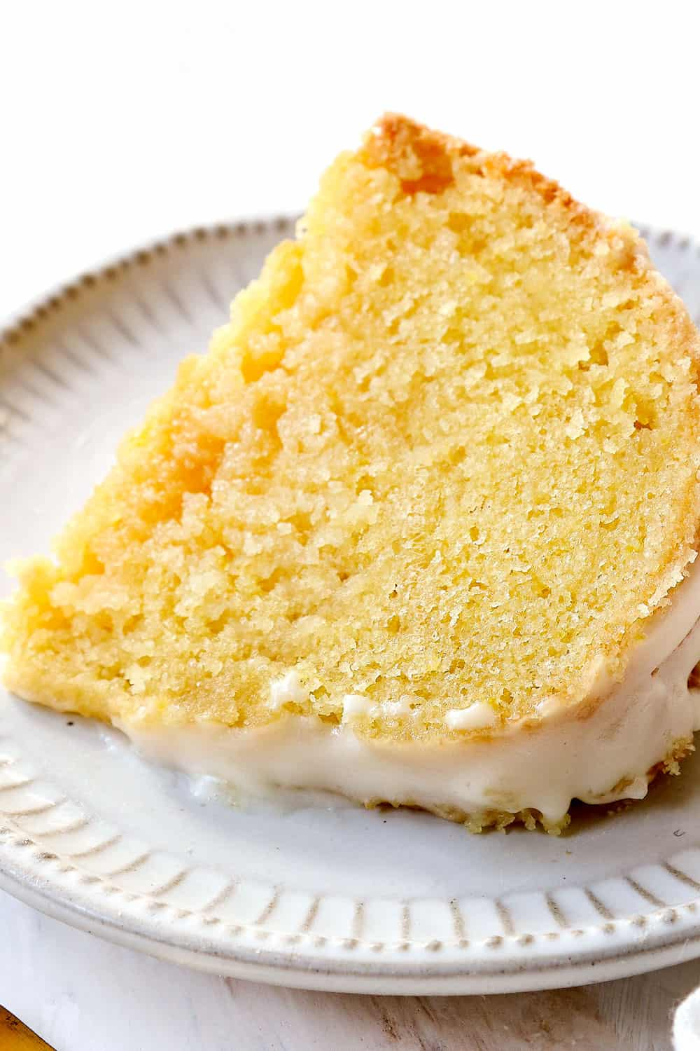 a slice of lemon pound cake laying on on a plate showing how moist it is