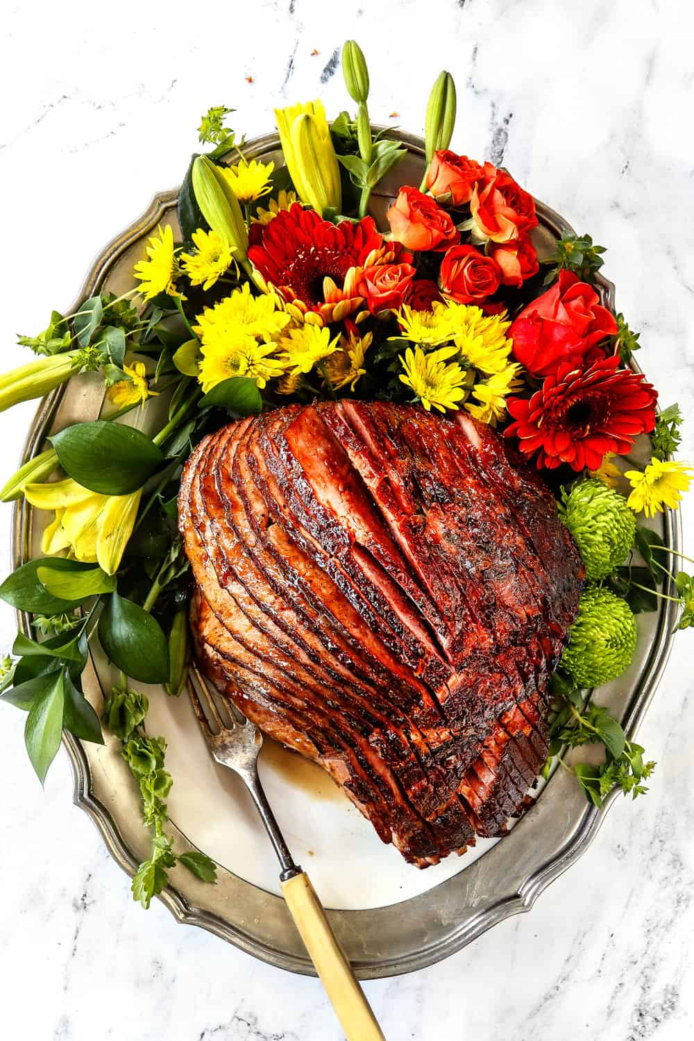 Ham glaze recipe with brown sugar and pineapple on a platter with leaves and flowers