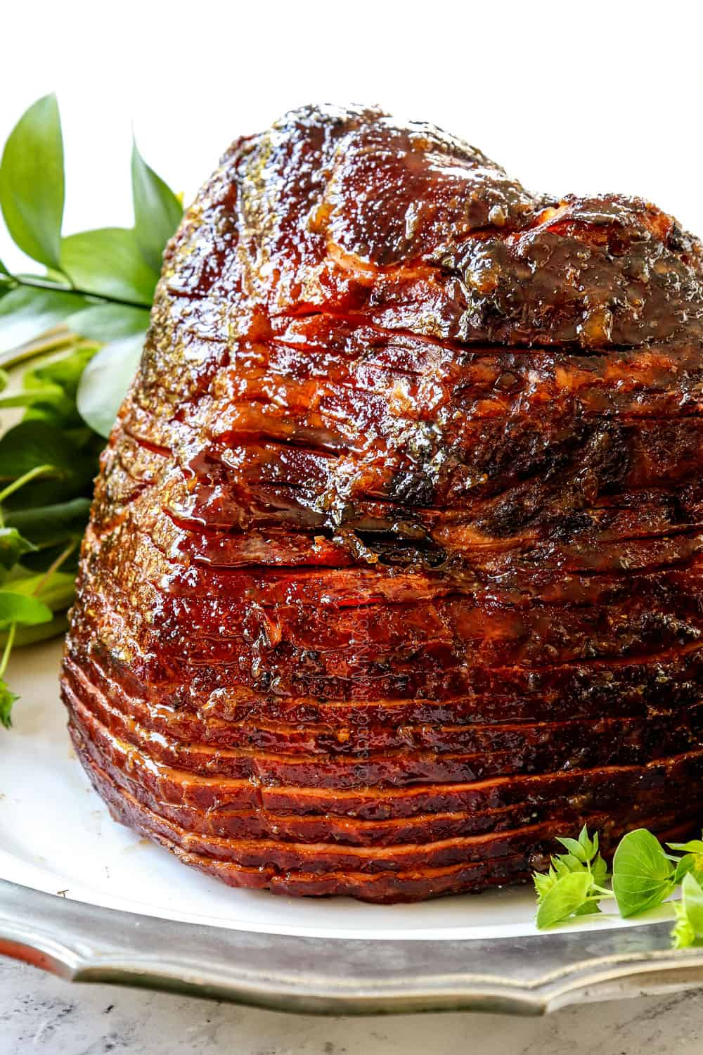 showing how to make spiral ham with brown sugar pineapple ham glaze by resting the ham on a white platter