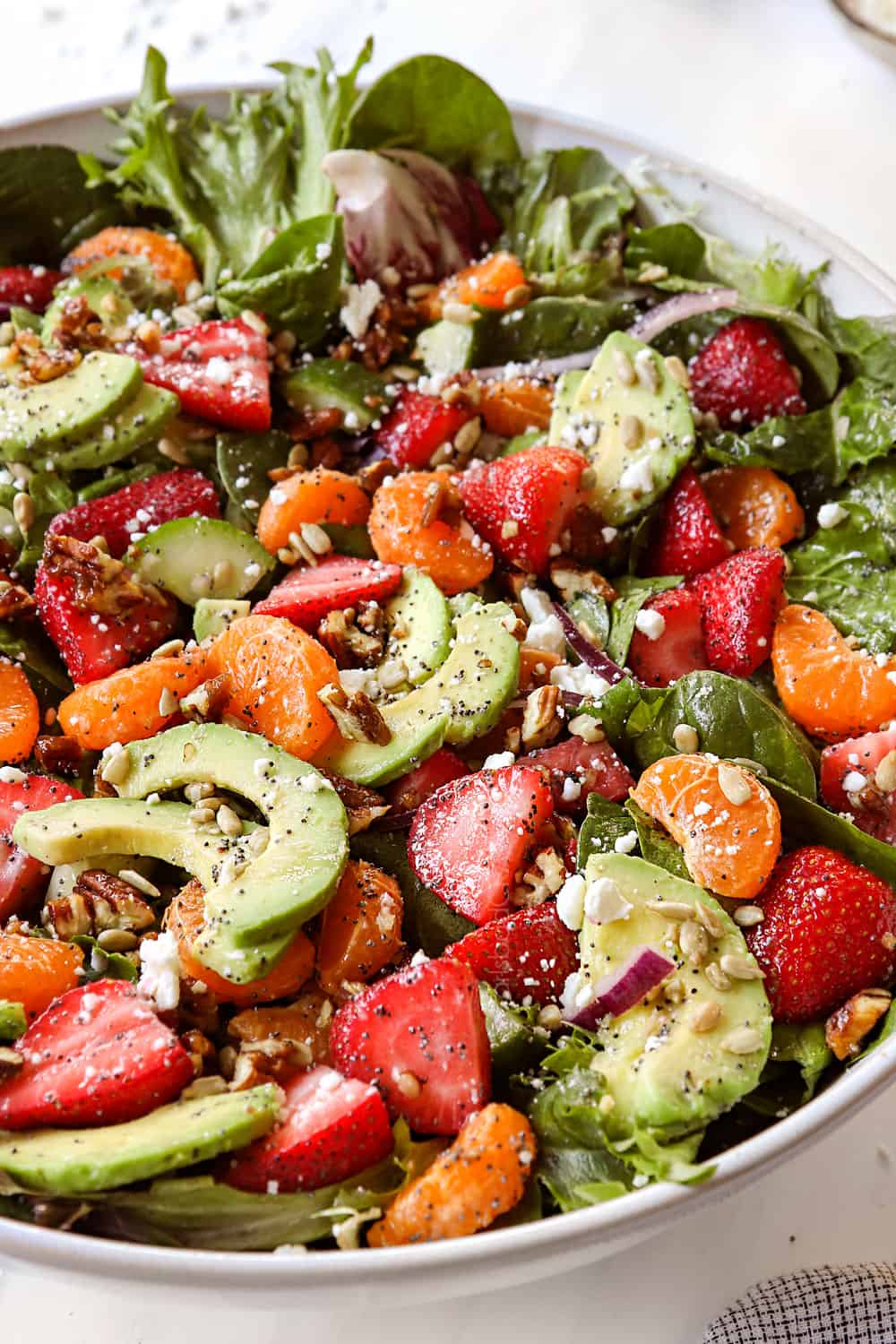 strawberry spinach salad recipe in a white bowl with candied nuts, feta and red onions
