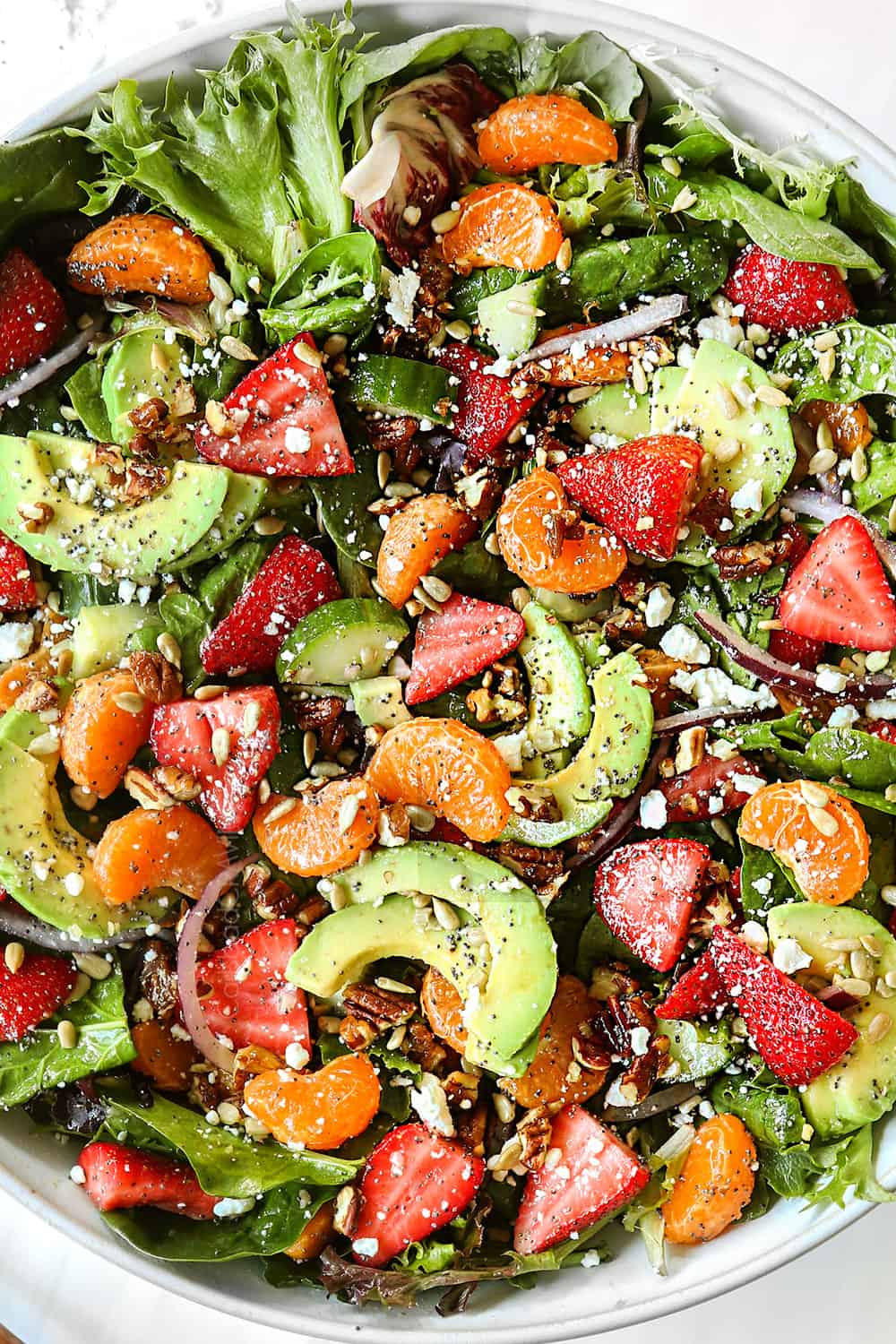 top view of spinach and strawberry salad recipe tossed in a bowl