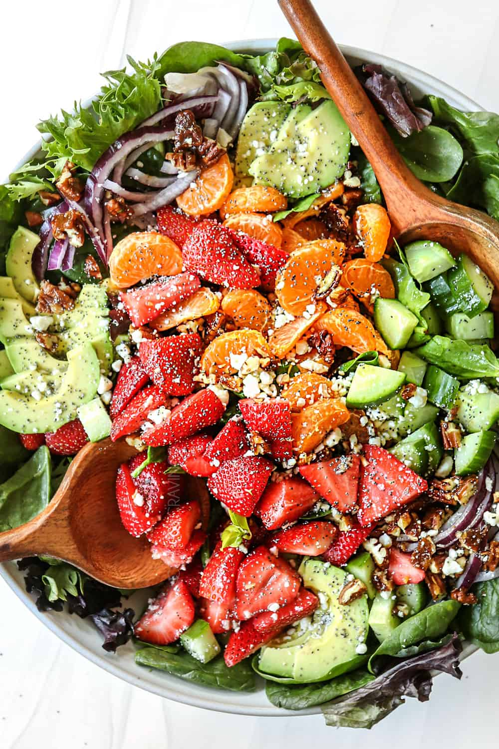 showing how to make strawberry spinach salad recipe by adding spinach, strawberries, clementine oranges, cucumbers, avocados and red onions to a bowl