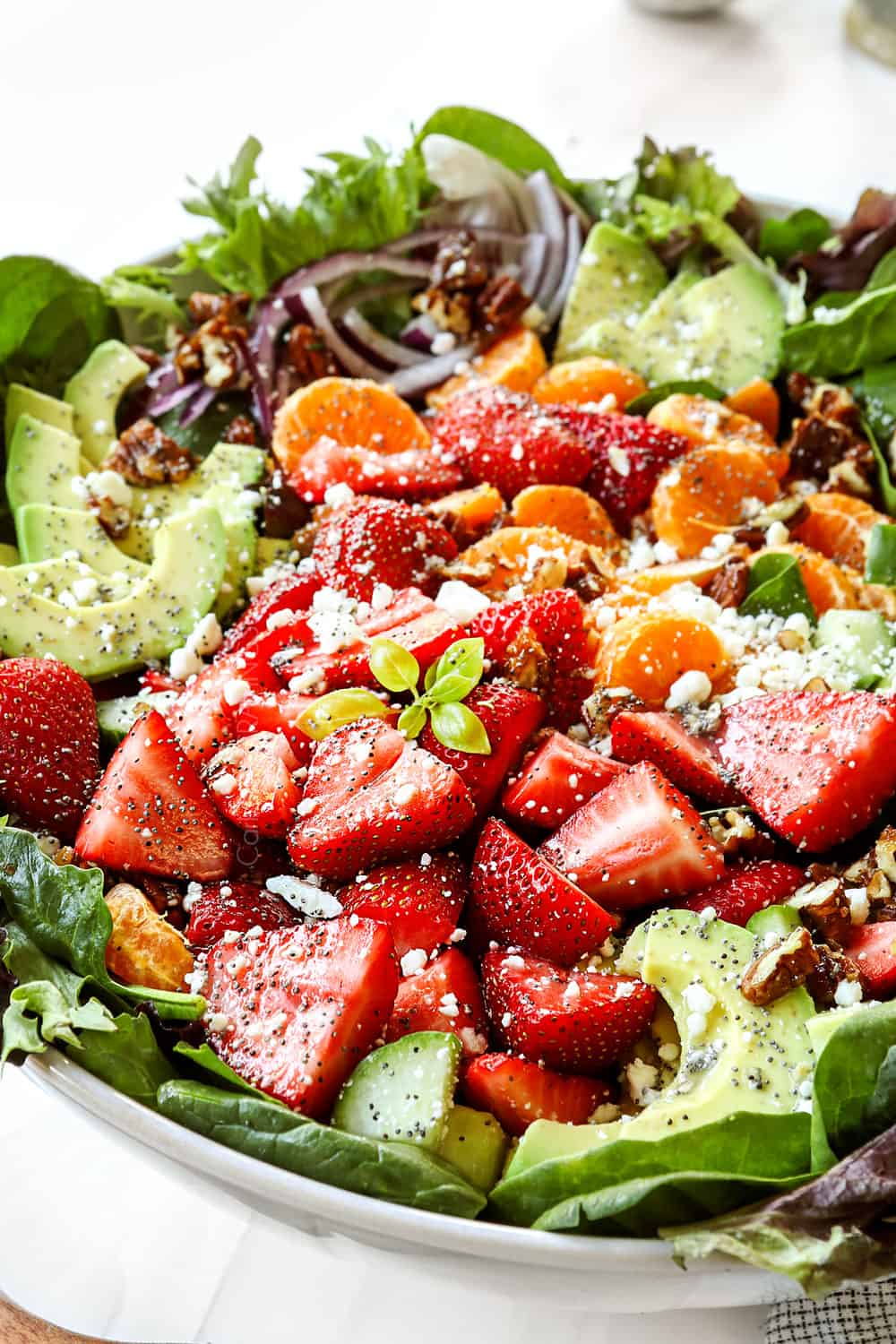 spinach and strawberry salad in a bowl with strawberries, candied nuts, red onions nd feta