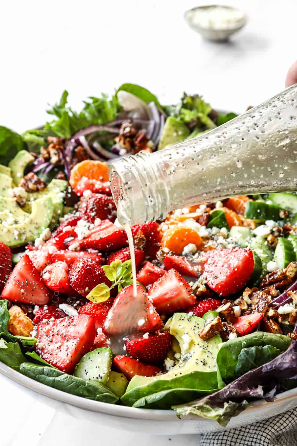 showing how to make strawberry spinach salad recipe by dressing with poppy seed vinaigrette