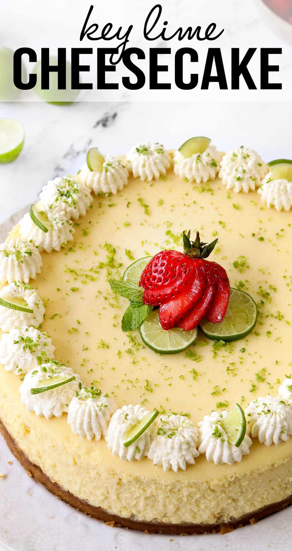 key lime cheesecake garnished with whipped cream, key limes and strawberries