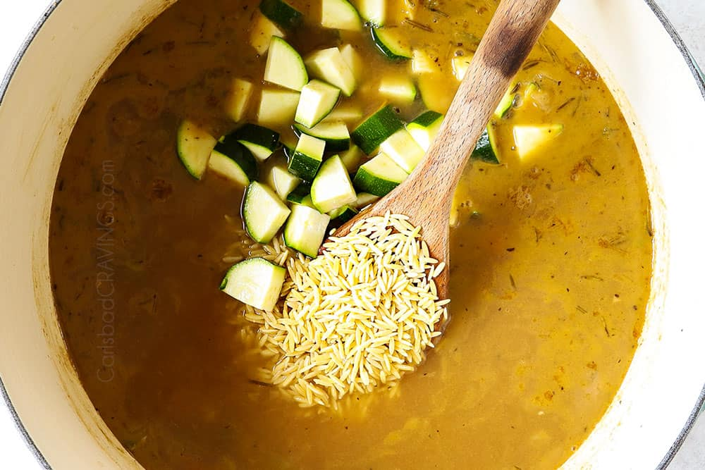 showing how to make lemon chicken orzo soup by adding orzo and zucchini to the soup