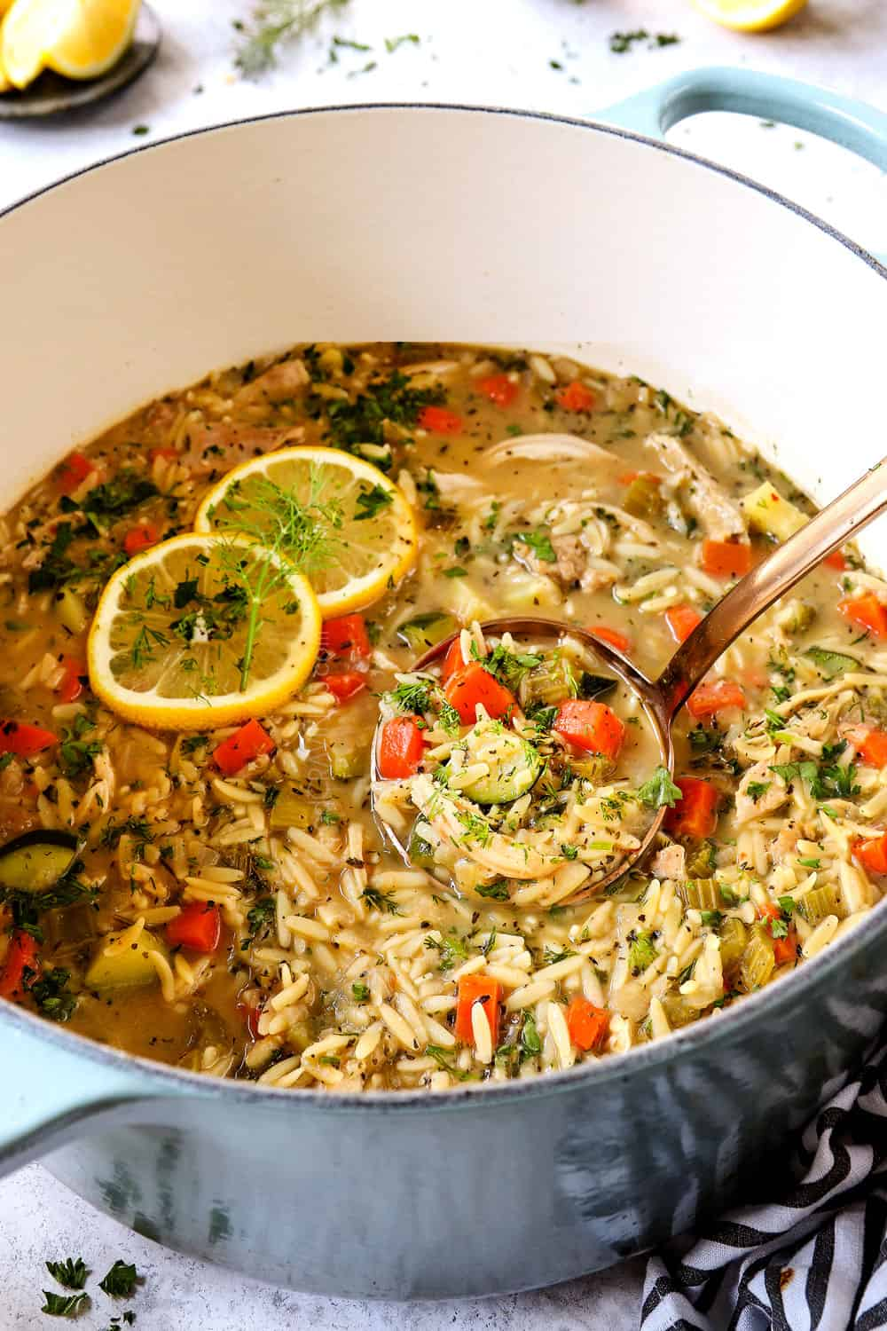 Greek lemon chicken orzo soup in a Dutch oven with fresh dill