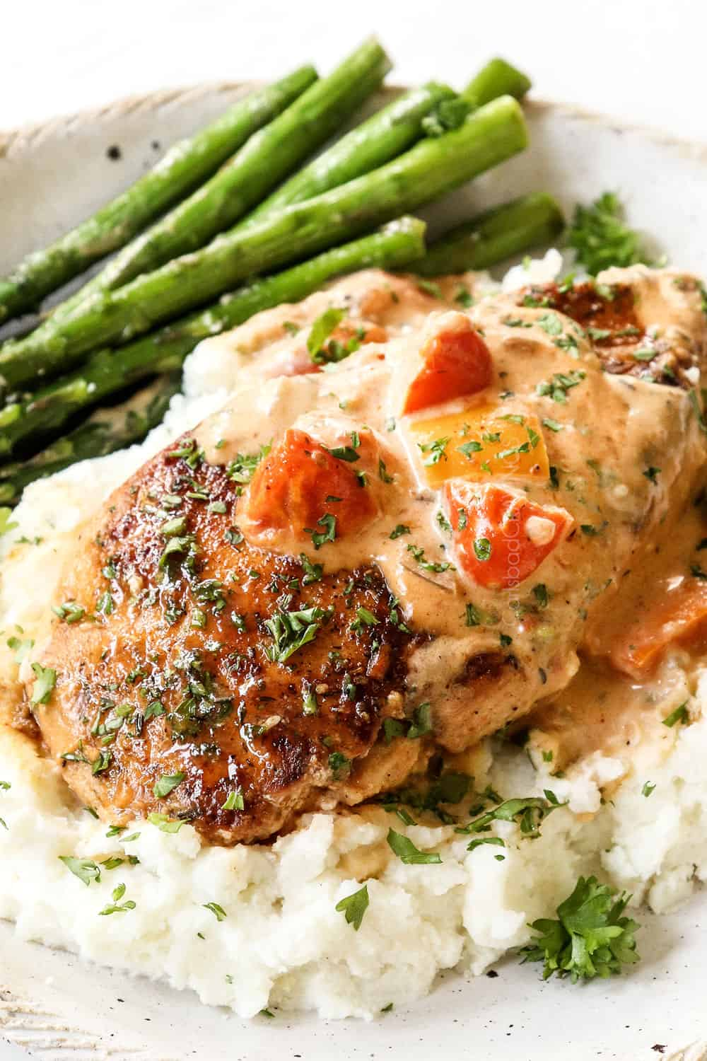 up close of a piece of Cajun chicken on a plate with mashed potatoes and asparagus