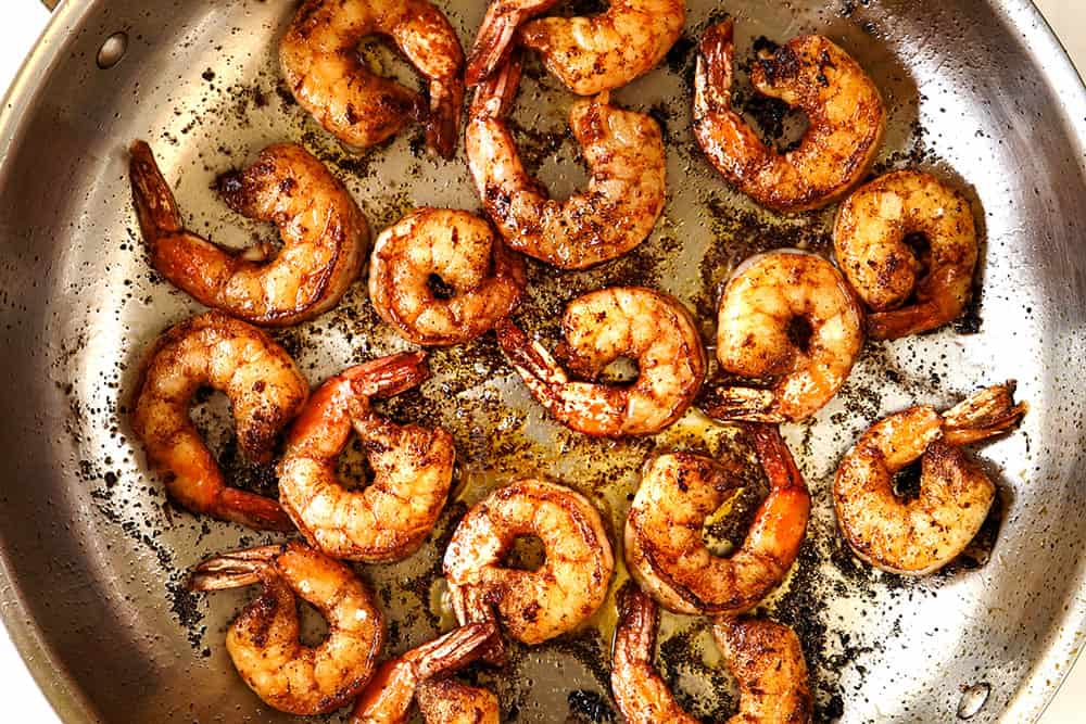 showing how to make easy shrimp taco recipe by cooking shrimp in a skillet in a single layer