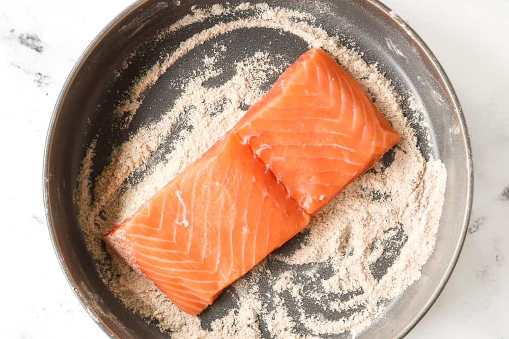 showing how to make honey glazed salmon recipe by dredging salmon fillet in flour and seasonings