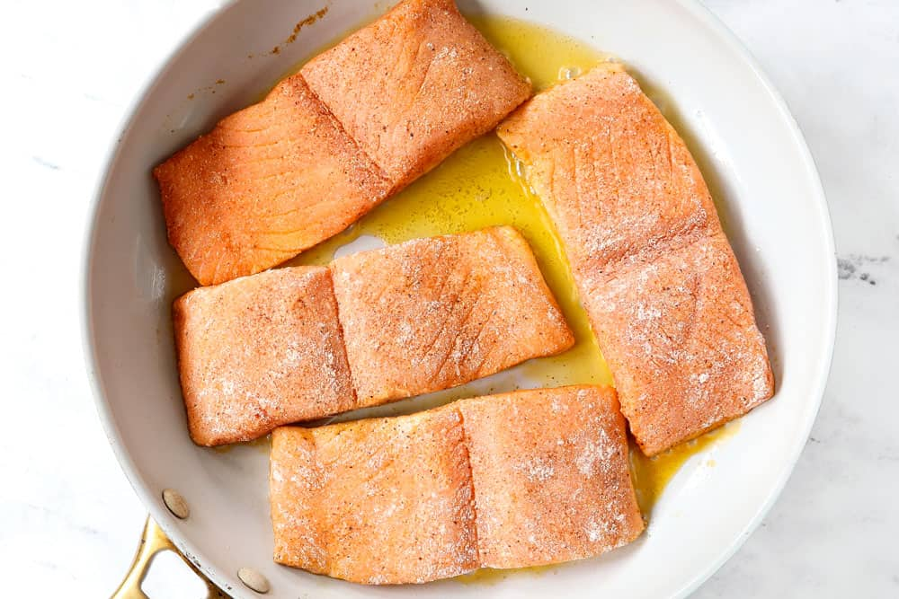 showing how to make honey glazed salmon recipe by searing the salmon in a skillet with vegetable oil