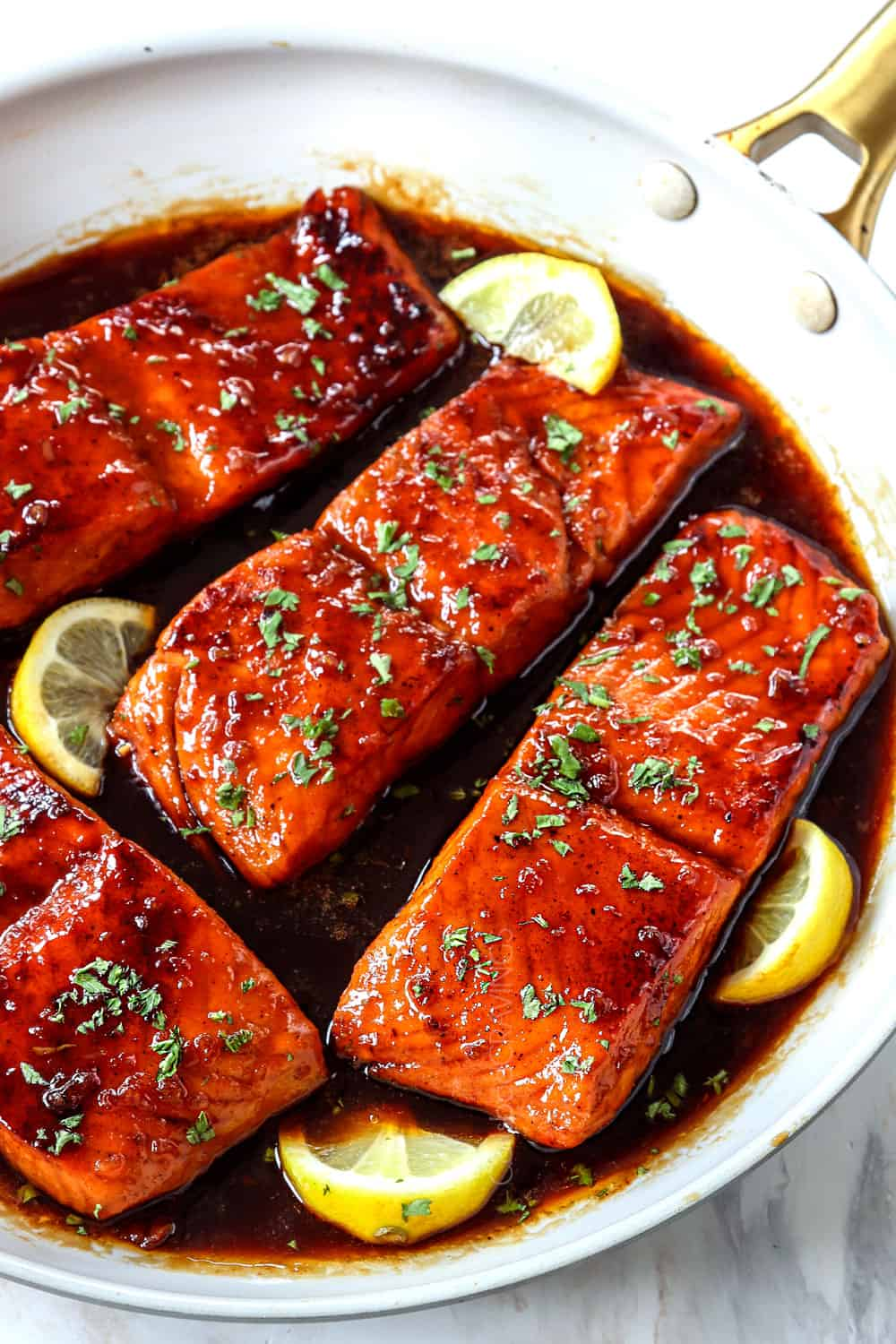 showing how to make honey garlic glazed salmon by drizzling salmon with honey garlic sauce while simmering in the skillet
