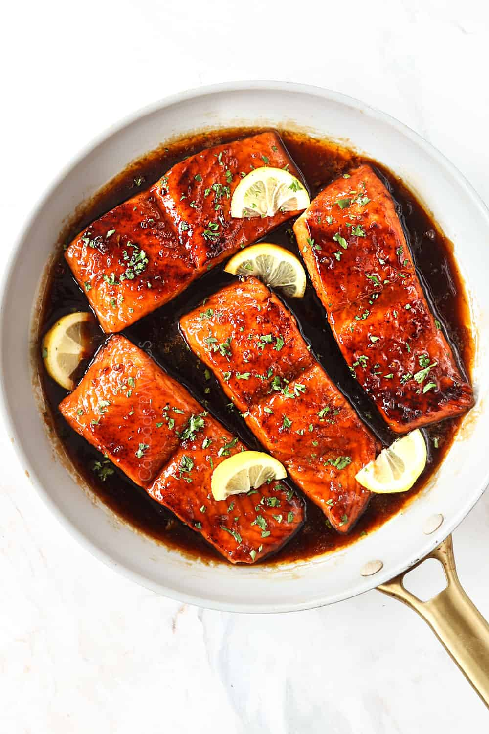 top view of honey garlic glazed salmon in a white skillet garnished by parsley