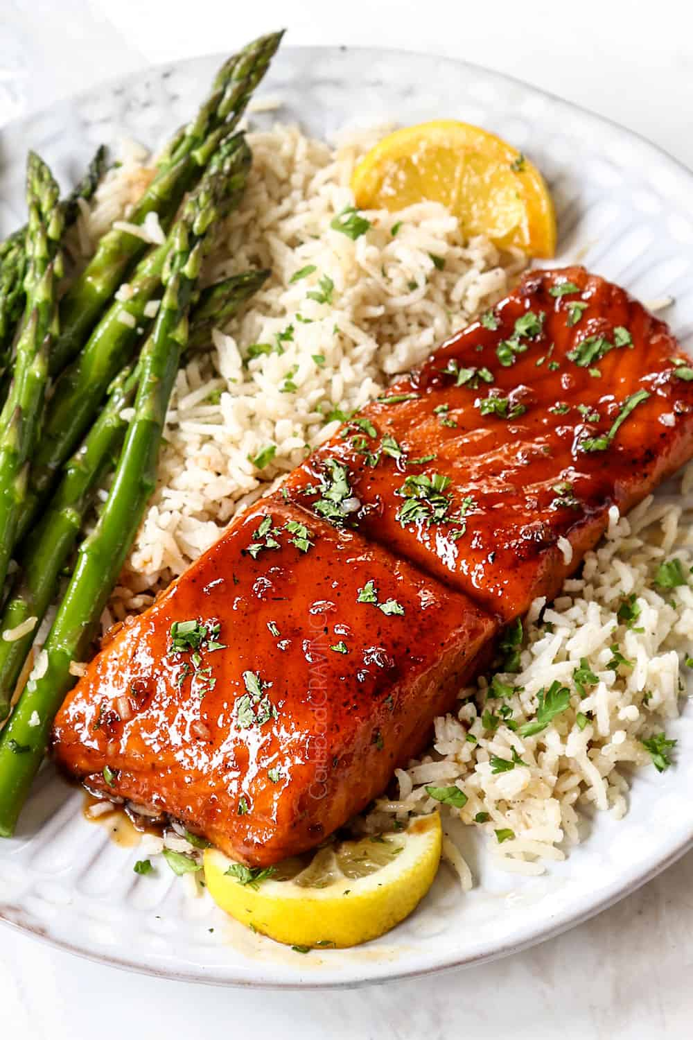 showing how to serve honey garlic glazed salmon by serving on a white plate with jasmine rice, asparagus and lemon wedges garnished by chopped parsley,