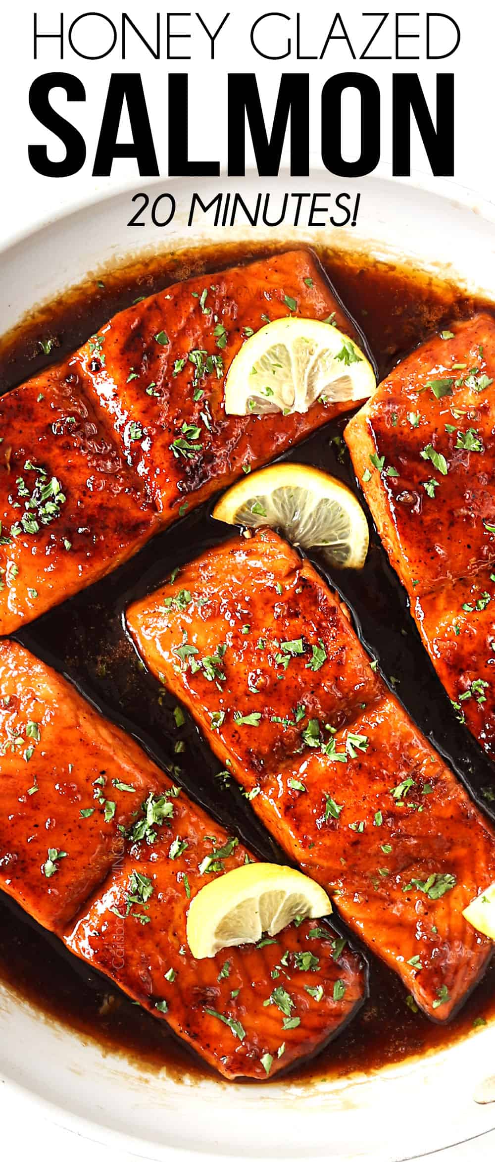 top view of honey garlic salmon in a white skillet garnished by lemon wedges