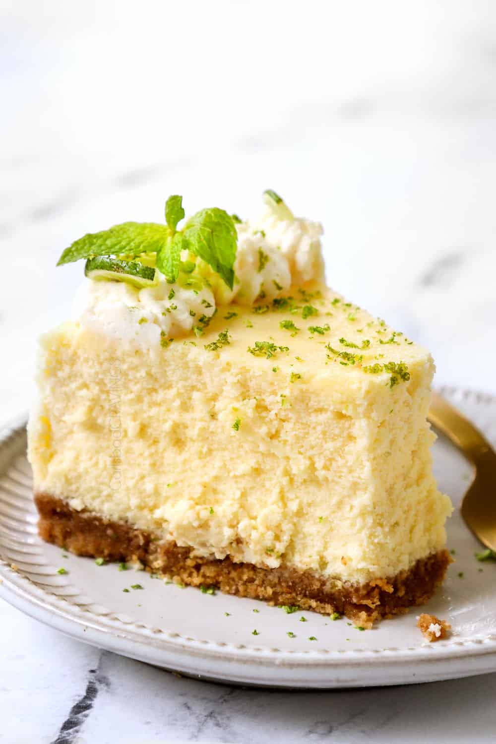 a slice of key lime cheesecake with a bite taken out of it showing how creamy it is