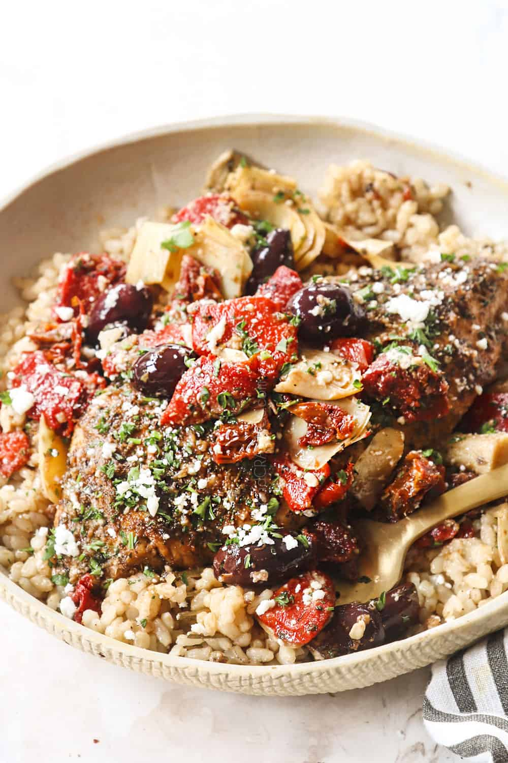 showing how to make Greek chicken recipe by adding to a plate with rice, tomatoes, olives and feta