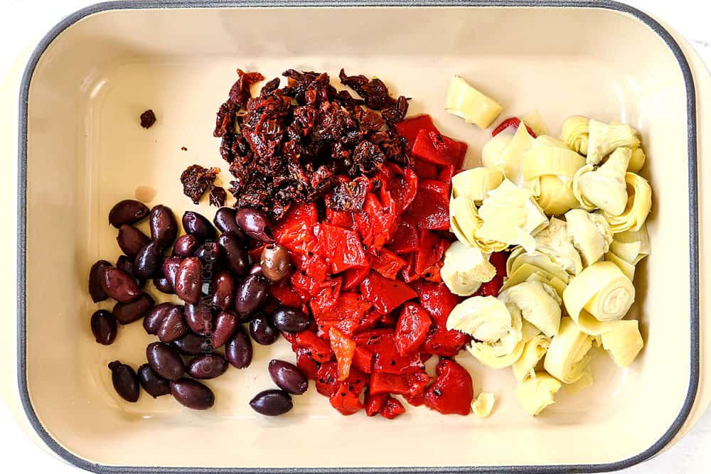 showing how to make Greek chicken by adding sun-dried tomatoes, Kalamata olives, artichokes and roasted red bell peppers to a baking dish