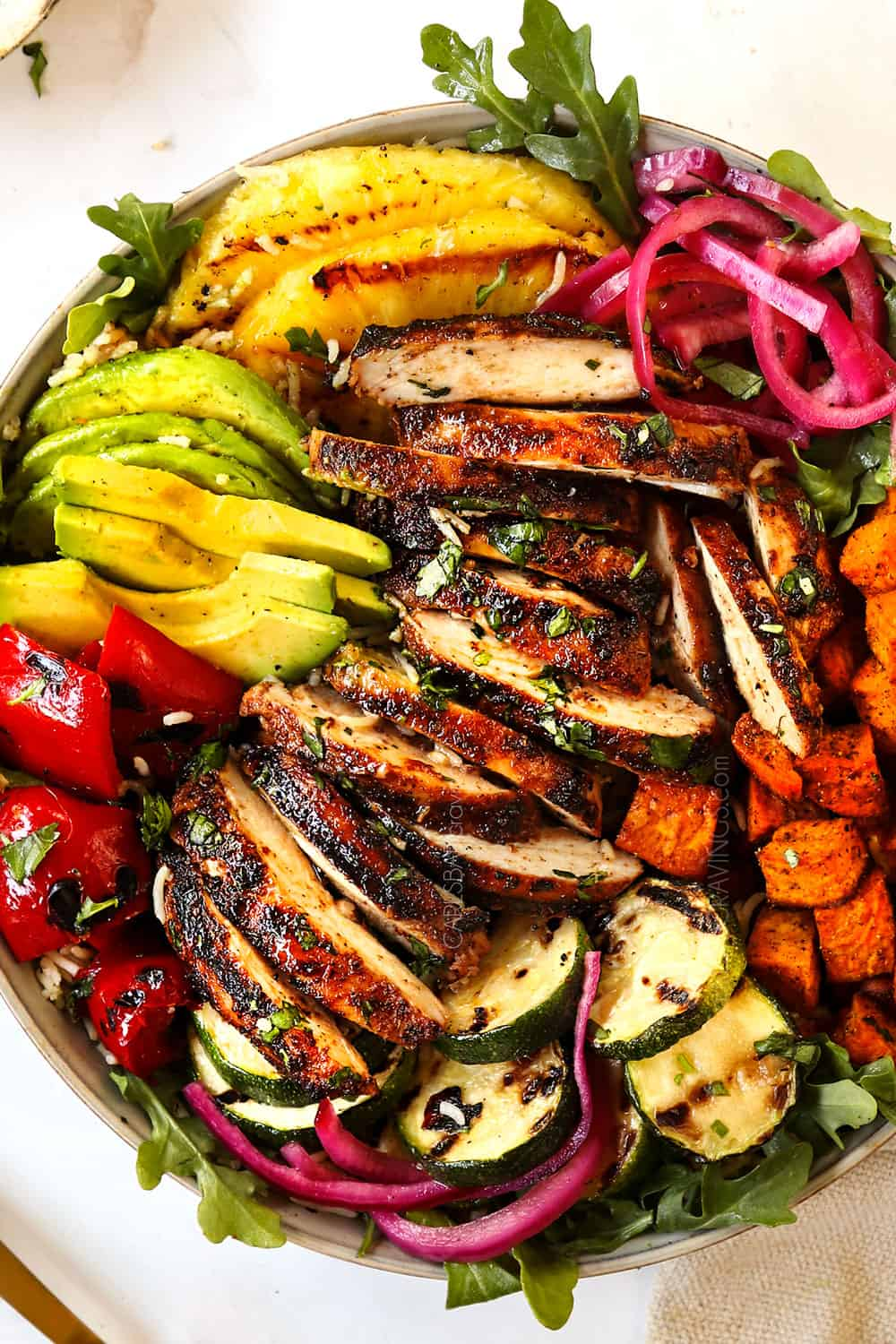 top view of harissa chicken thighs in a bowl with bell peppers, sweet potatoes and pickled red onions showing how to serve the recipe