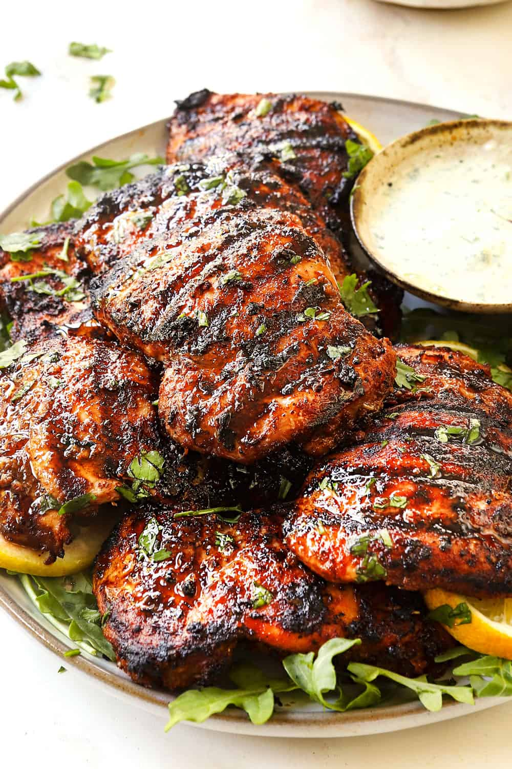 up close of harissa chicken thighs on a platter showing how juicy they are