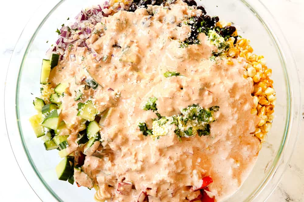 showing how to make Mexican Pasta Salad by adding the pasta salad dressing to the ingredients in a glass bowl
