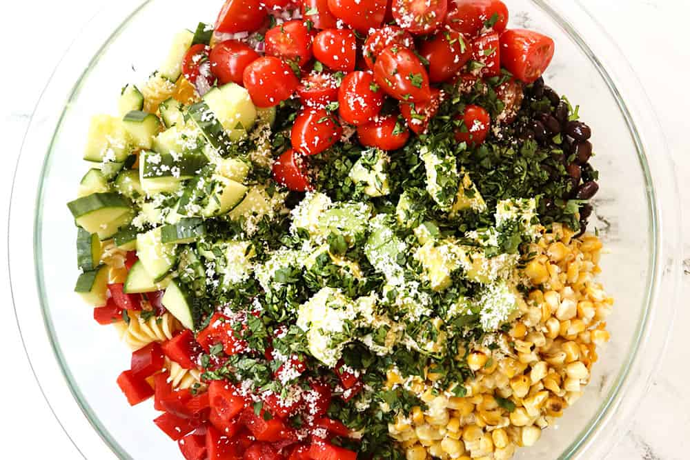 showing how to make Mexican Pasta Salad by adding all of the pasta salad ingredients (tomatoes, cucumbers, bell peppers, black beans, jalapenos, cilantro, corn, Cotija Cheese) to a glass bowl