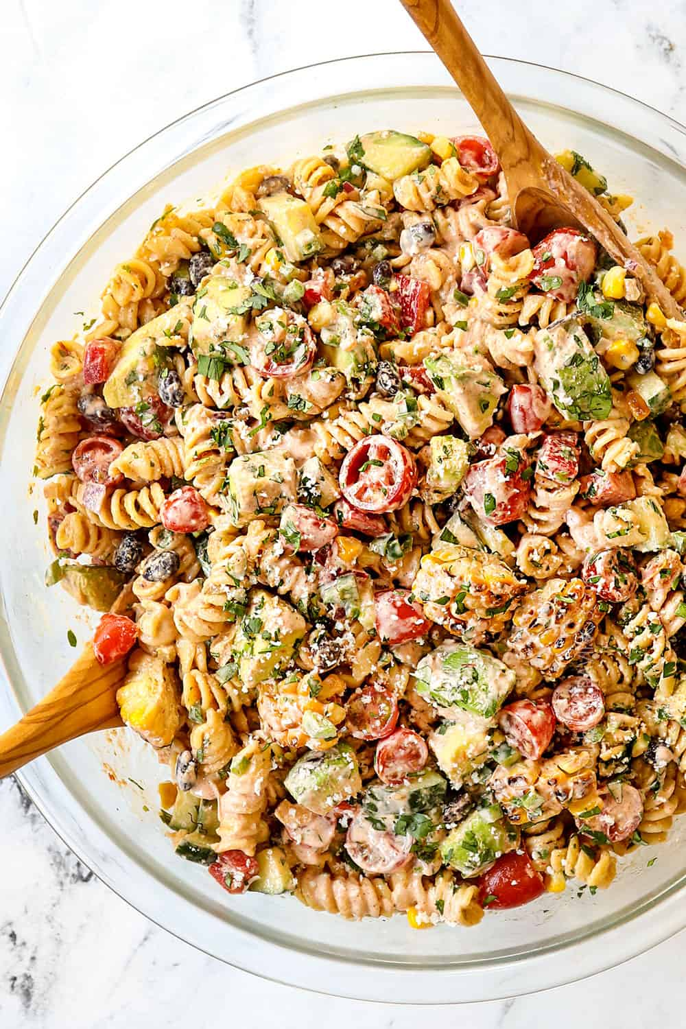 showing how to make Mexican Pasta salad by tossing the dressing and the ingredients together in a glass bowl
