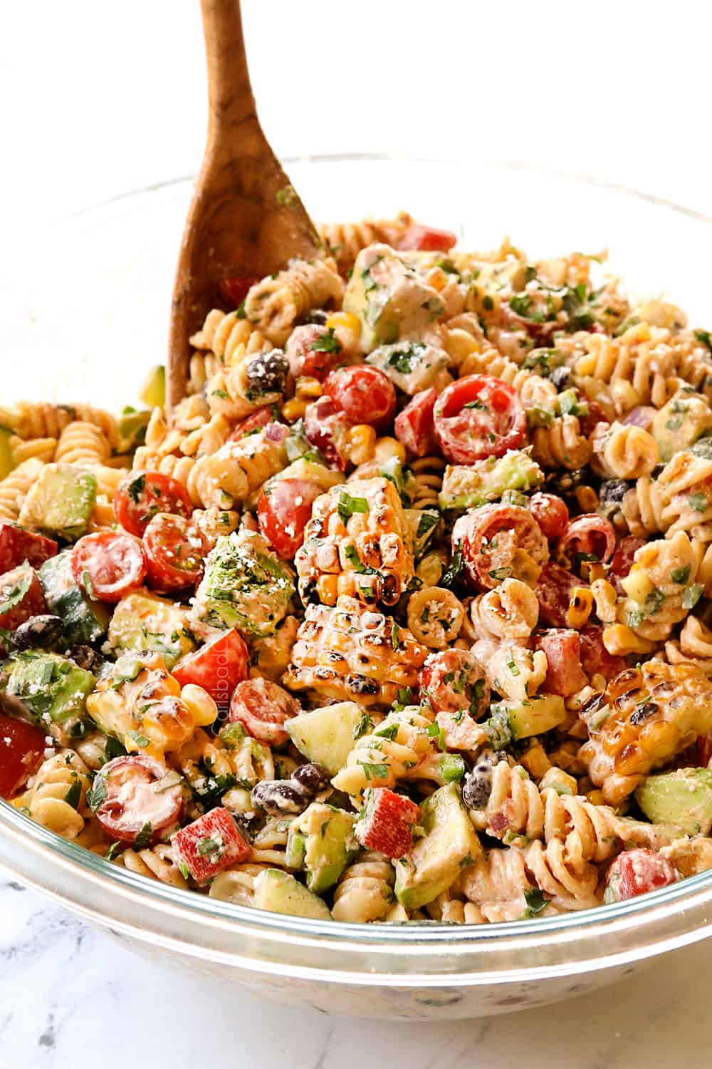 tossing Mexican pasta salad together in a glass bowl