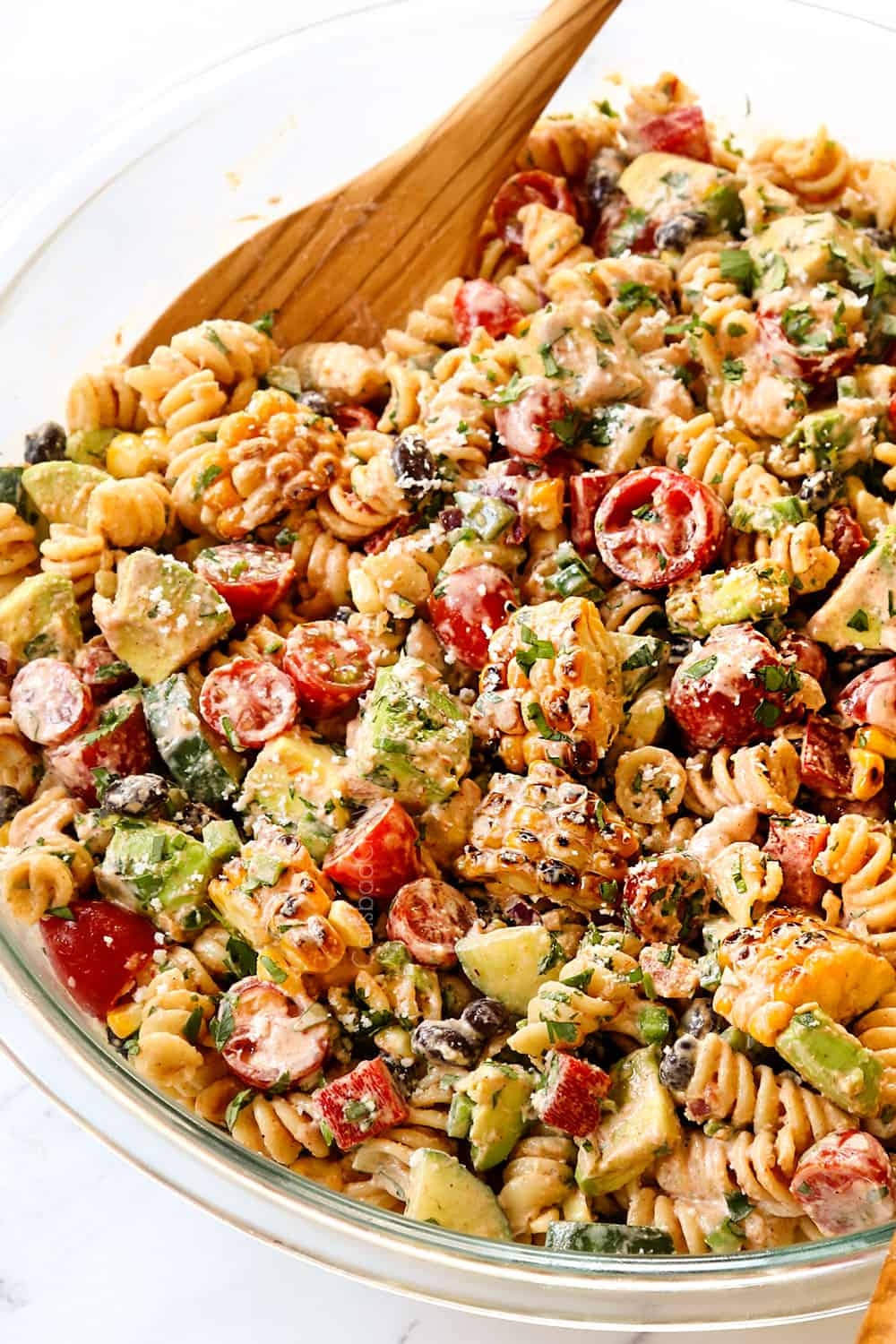 Mexican Pasta Salad in a glass bowl with wooden spoons