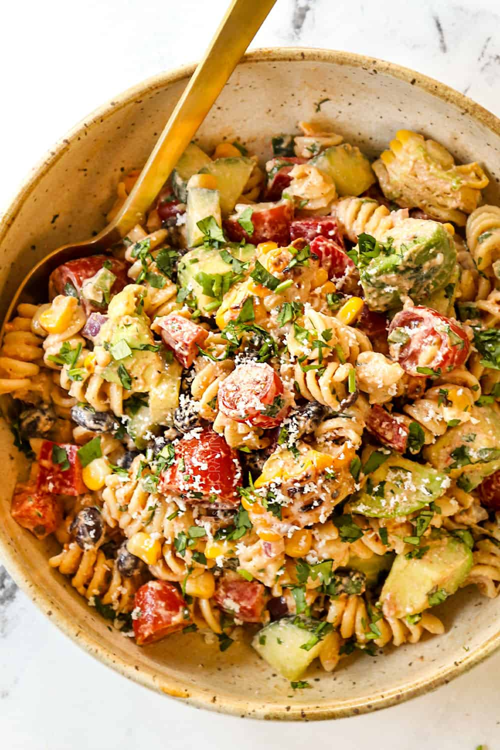 showing how to serve Mexican pasta salad by adding to a small bowl and garnishing with cilantro and Cotija cheese