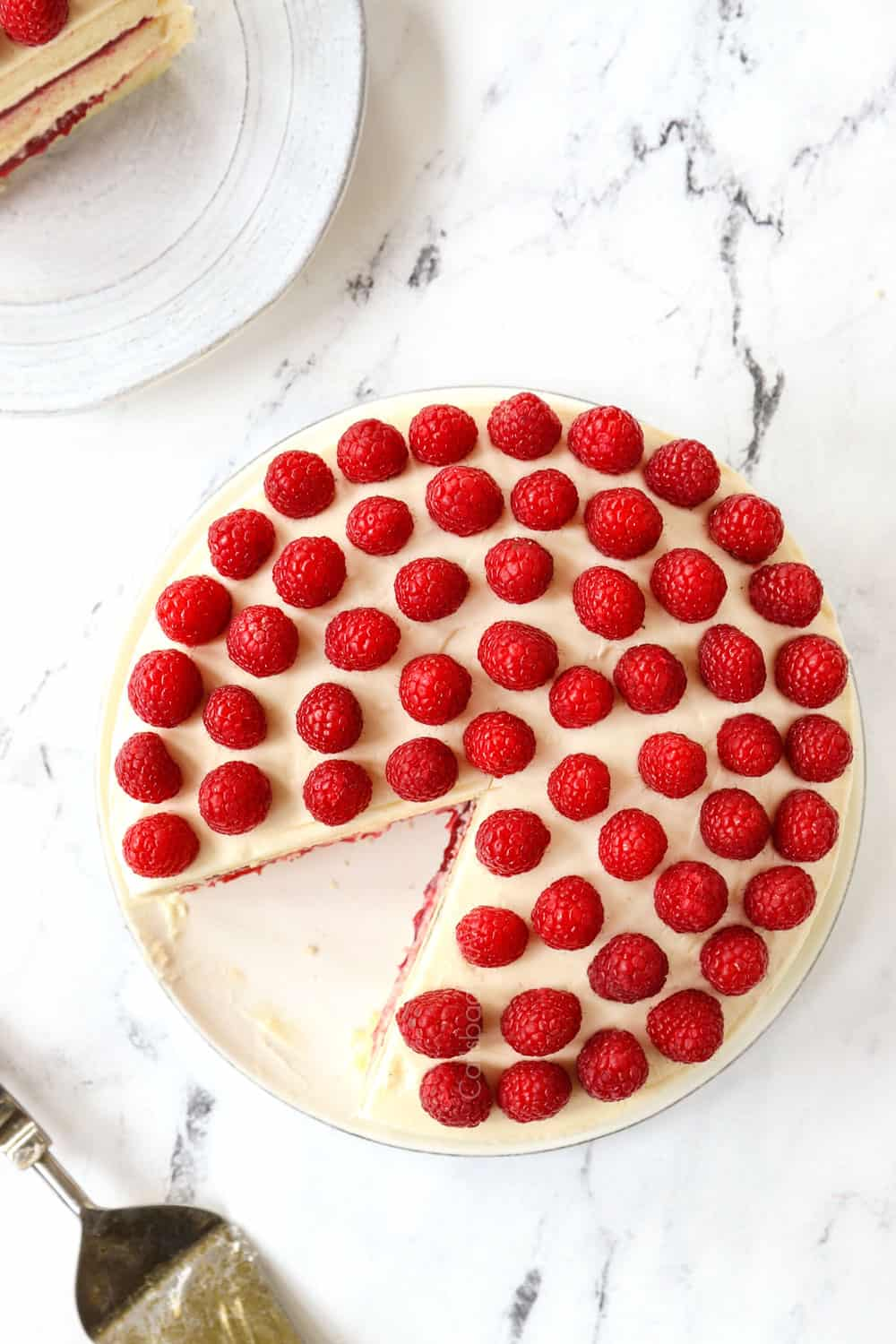 top view of white cake garnished with raspberries on top