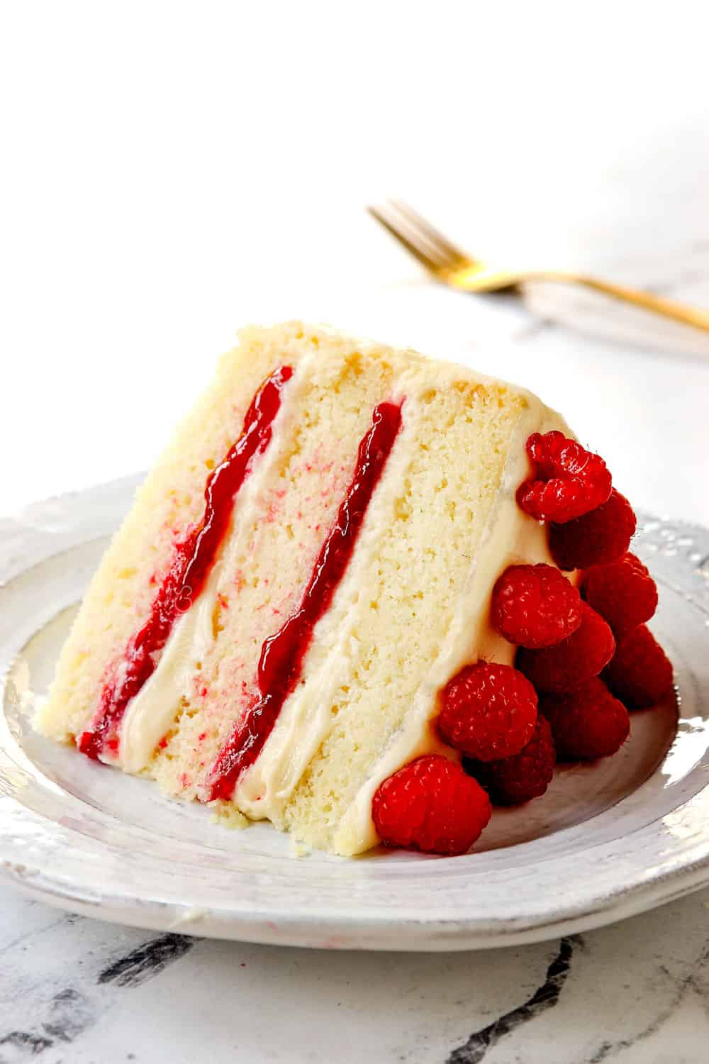 a slice of white chocolate raspberry cake showing how tender it is