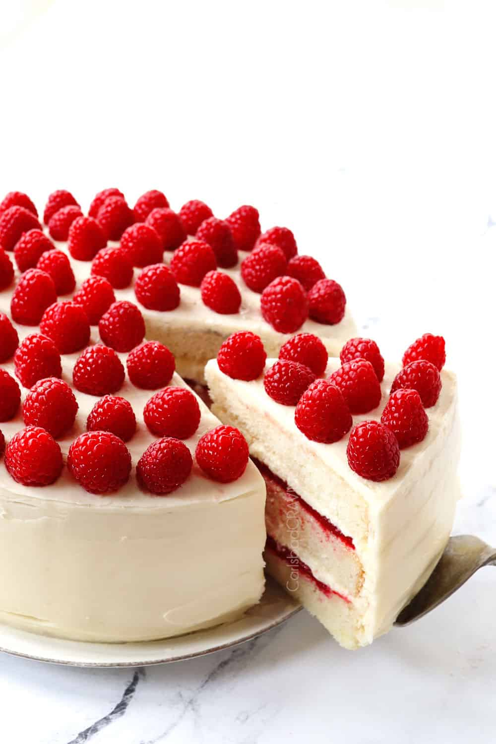 pulling out a piece of white chocolate raspberry cake