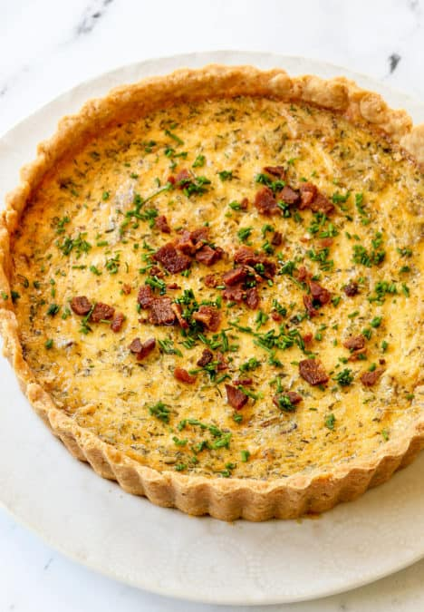 top view of Quiche Lorraine garnished with chives on a white plate