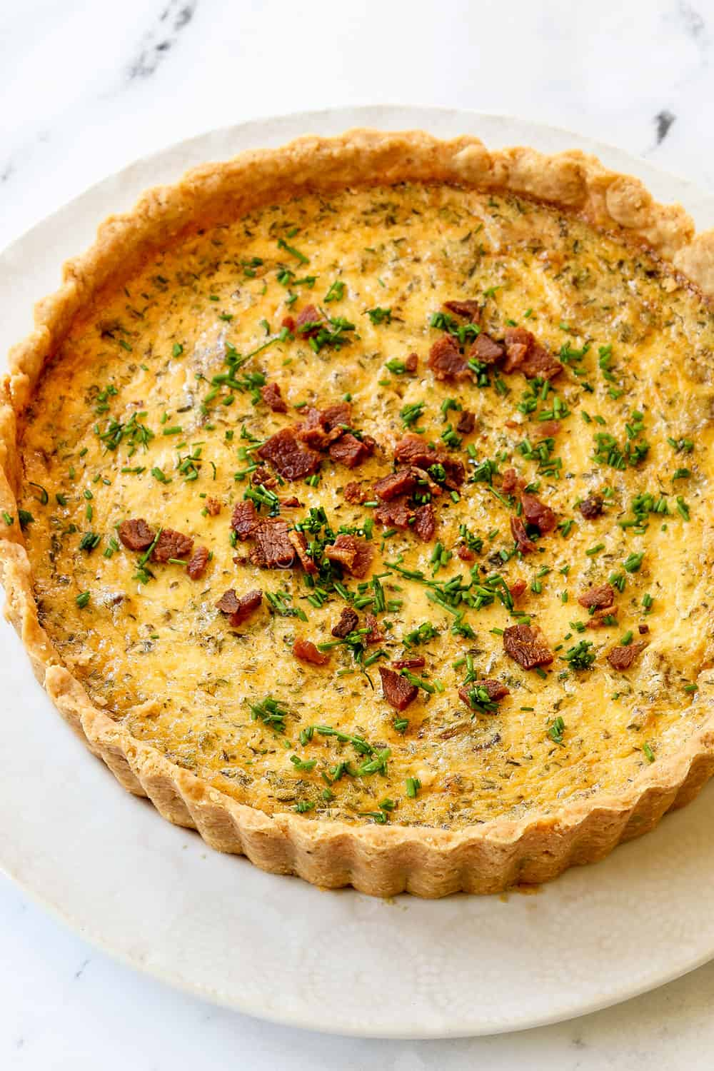 Quiche Lorraine recipe on a white plate garnished with chives on a white plate