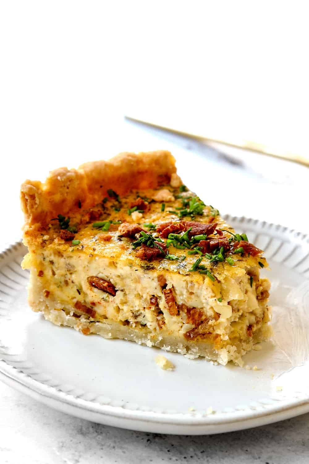 up close of best Quiche Lorraine with a bite taken out of it