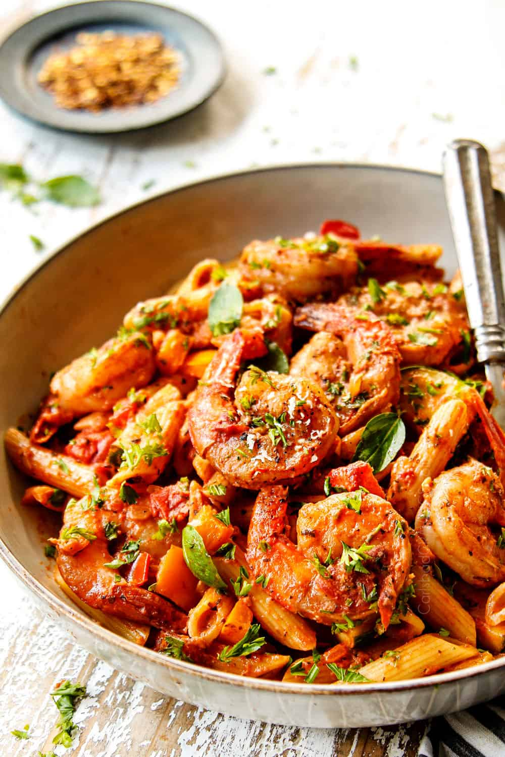 showing how to make shrimp pasta by adding to a bowl