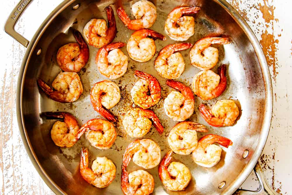 showing how to make shrimp pasta by sauteing shrimp in a stainless steel skillet