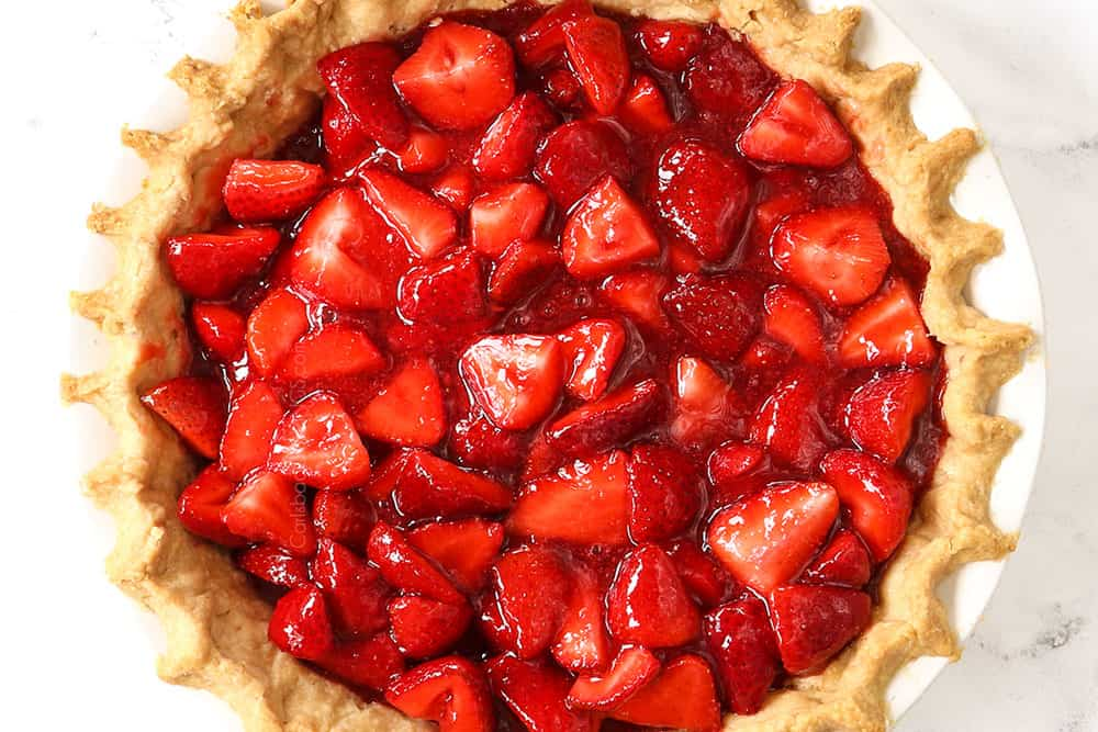 showing how to make fresh strawberry pie recipe by adding strawberry pie filling to the pie shell to chill